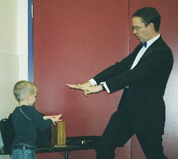 Richard Young the Magician teaching the birthday boy a trick